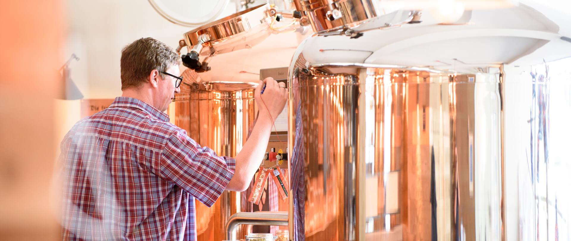 Bier-Brauerei Garmischer Brauprozess Mann an Brauanlage
